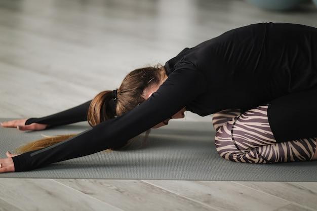 Jovem mestre de ioga gravando conteúdo de vídeo de seu exercício para seu curso online com o telefone no tripé. treinamento feminino atlético em estúdio. Foto Premium