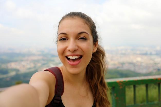 Jovem mochileira sorridente tira um autorretrato no pico do jaraguá com o horizonte da metrópole de são paulo ao fundo, brasil Foto Premium