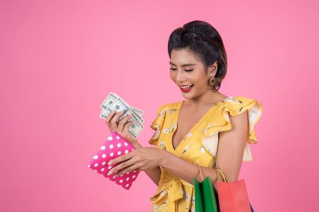 Jovem moda mulher mão segurando carteira e sacolas de compras Foto gratuita
