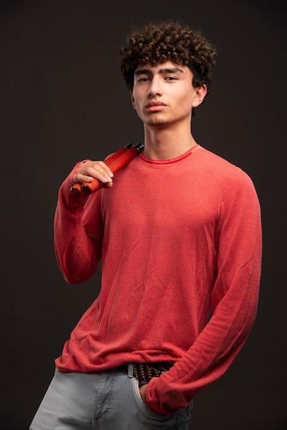 Jovem modelo de camisa vermelha segurando karate nunchaku. Foto gratuita