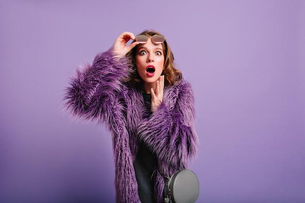 Jovem modelo feminina surpresa com bolsa cinza elegante posando no estúdio roxo Foto gratuita
