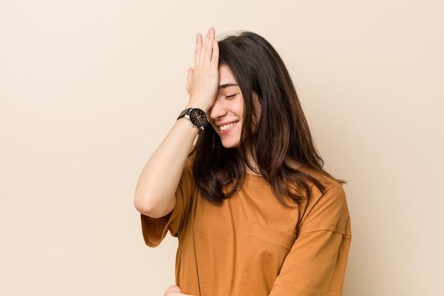 Jovem morena contra uma parede bege, esquecendo algo, batendo na testa com a palma da mão e fechando os olhos. Foto Premium