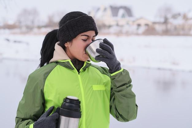 Jovem morena de jaqueta verde em winter park bebendo chá quente em uma garrafa térmica. Foto Premium