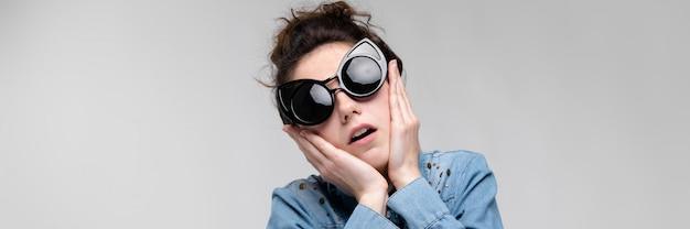 Jovem morena de óculos escuros. óculos de gato. o cabelo está reunido em um coque. a mulher está segurando o rosto dela. Foto Premium