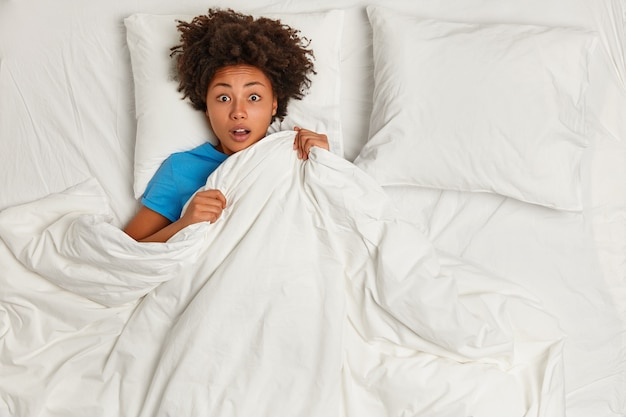 Jovem morena deitada na cama Foto gratuita
