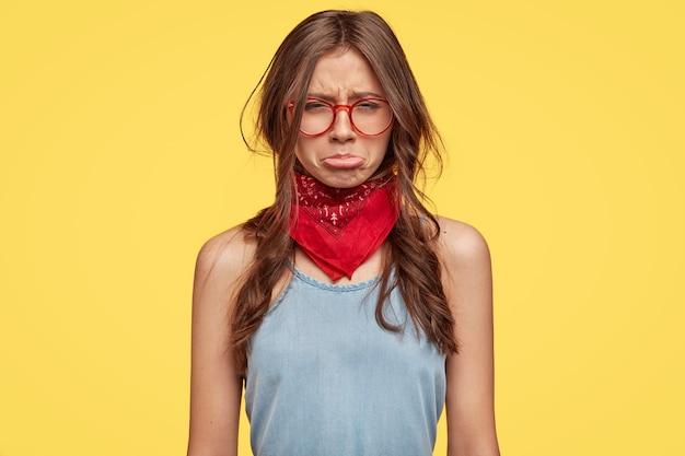 Jovem morena deprimida com óculos posando contra a parede amarela Foto gratuita