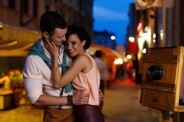 Jovem morena e bonitão, abraçando na rua à noite Foto Premium