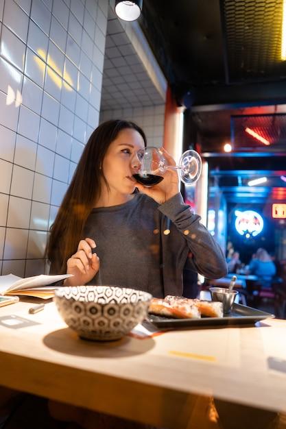 Jovem morena linda bebe vinho em um café Foto gratuita