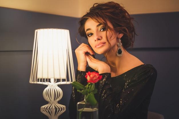 Jovem morena linda com cabelo encaracolado sentado no café Foto Premium