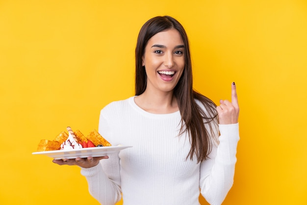 Jovem morena segurando waffles sobre parede isolada, apontando para cima uma ótima idéia Foto Premium