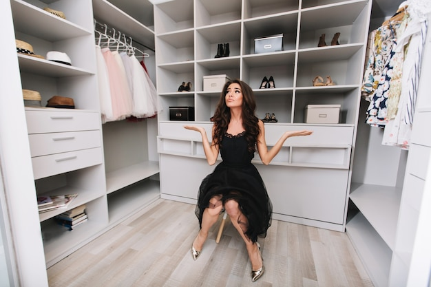 Jovem morena sentada em um enorme camarim pensa na escolha de roupas, ela está vestida com uma roupa preta elegante e sapatos prateados, expressando verdadeiras emoções positivas do rosto. Foto gratuita