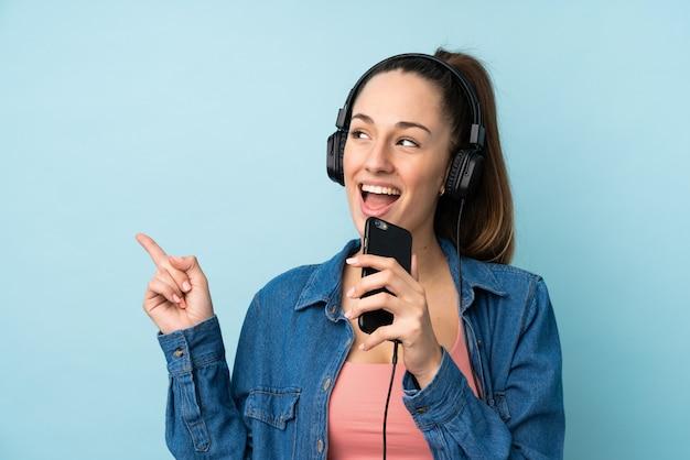 Jovem morena sobre música de parede azul isolado com um celular e cantando Foto Premium