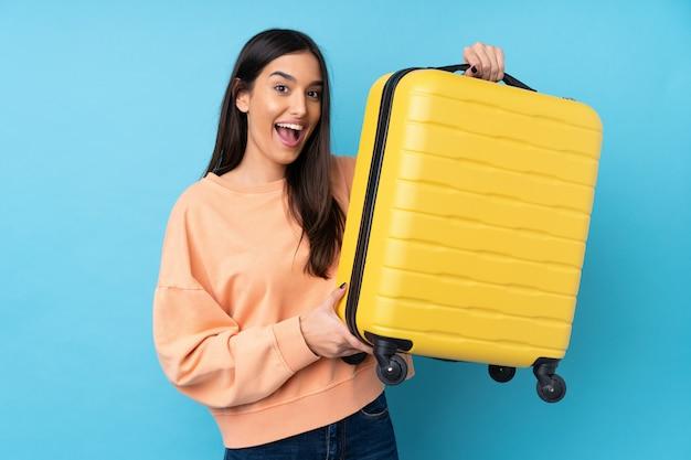 Jovem morena sobre parede azul isolada em férias com mala de viagem Foto Premium