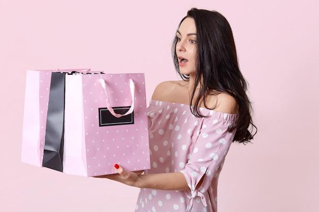 Jovem morena surpresa respirou fundo, detém muitas malas, retorna de uma loja com muitas compras, vestida com um vestido de bolinhas, isolado na rosada. conceito de compras Foto gratuita