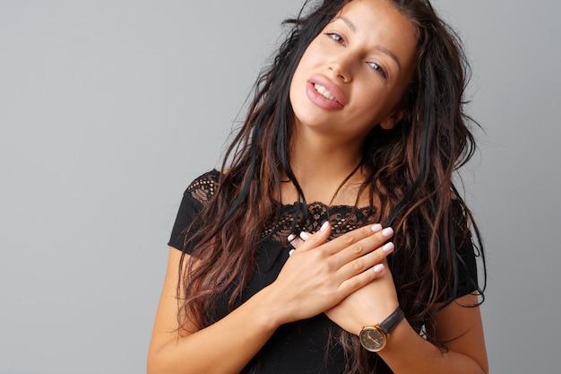 Jovem morena tocando seu coração com as mãos Foto Premium