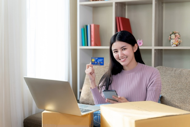 Jovem mostra cartão de crédito na mão para fazer compras on-line Foto gratuita