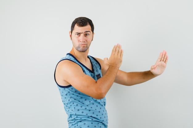 Jovem mostrando gesto de golpe de caratê em camiseta azul e parecendo estrito. vista frontal. Foto gratuita