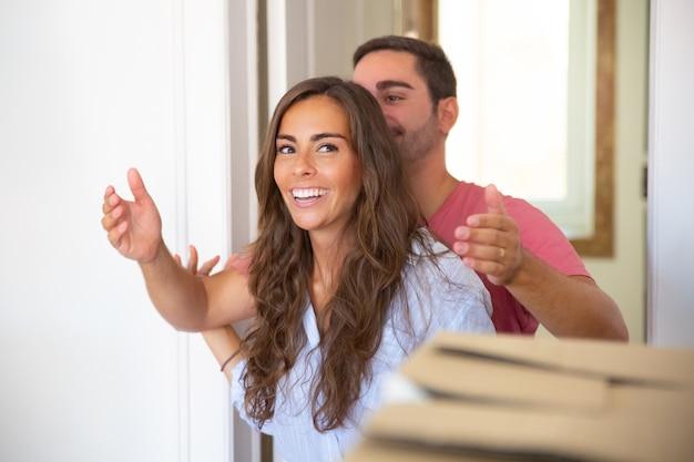 Jovem mostrando novo apartamento para sua namorada feliz e surpresa Foto gratuita