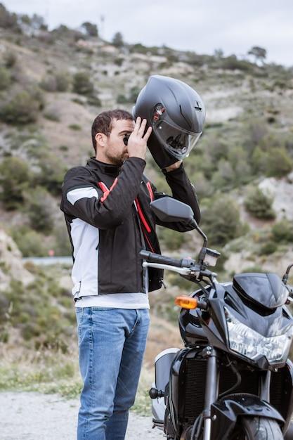 Jovem motociclista masculina colocando em seu capacete para dirigir sua moto Foto Premium
