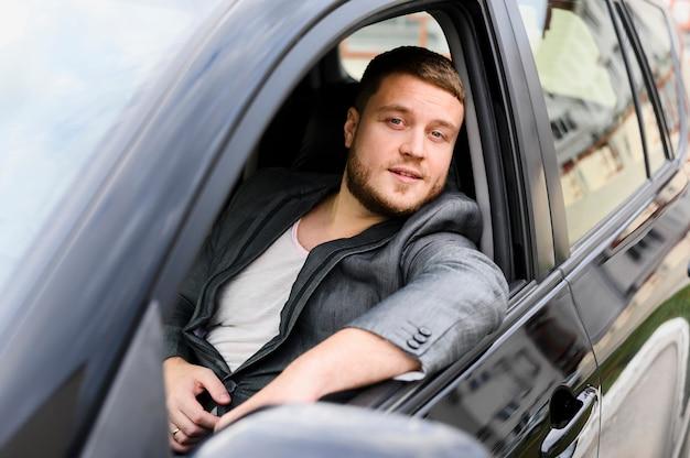 Jovem motorista com a janela do carro aberta Foto gratuita