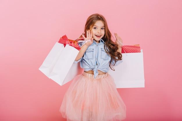 Jovem muito alegre em saia de tule, com longos cabelos castanhos andando com pacotes brancos sobre fundo rosa. momentos adoráveis e doces da princesinha, criança muito simpática se divertindo com a câmera Foto gratuita