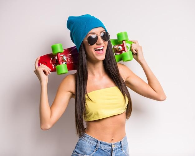 Jovem mulher à moda na roupa colorida com skate. Foto Premium