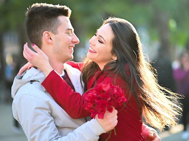 Jovem mulher abraçando o namorado porque ele lhe deu flores - conceito de dia dos namorados Foto Premium