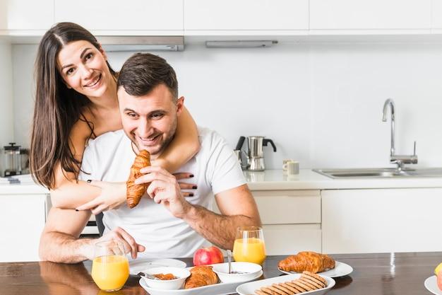 Jovem mulher abraçando o namorado tomando café da manhã na cozinha Foto gratuita