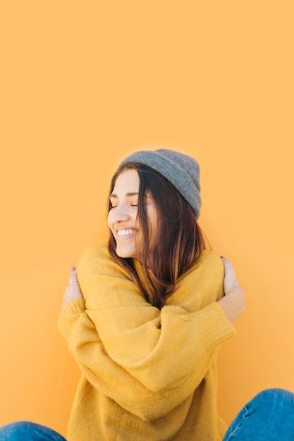 Jovem mulher abraçando-se com os olhos fechados Foto gratuita