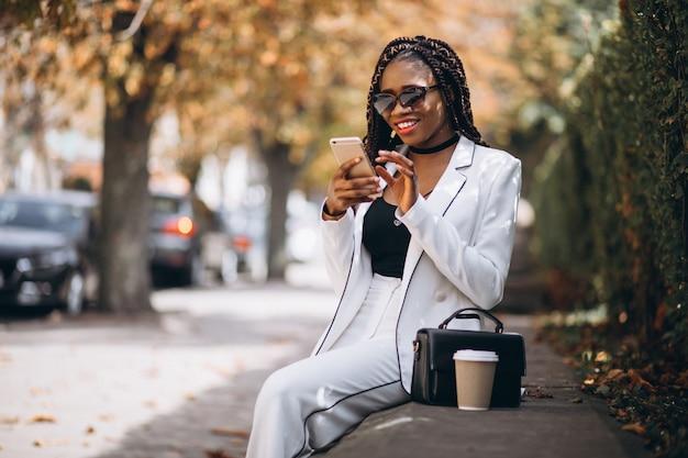 Jovem mulher africana, bebendo café e usando o telefone Foto gratuita