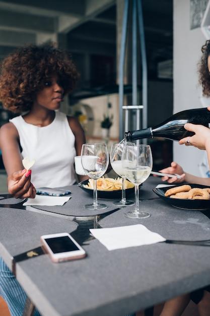 Jovem mulher africana bebendo vinho no restaurante moderno com amigos Foto Premium