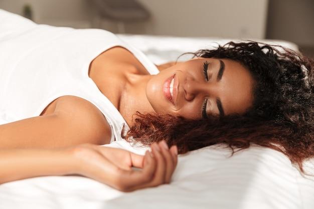 Jovem mulher africana desfrutar do sol na cama Foto gratuita
