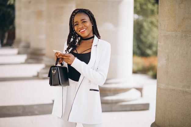 Jovem mulher africana em terno branco usando o telefone Foto gratuita