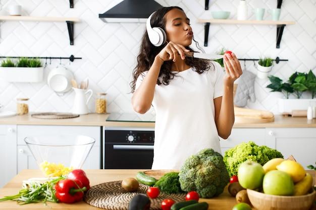 Jovem mulher africana emocional é ouvir música através de fones de ouvido e cantar corta um tomate cereja Foto gratuita