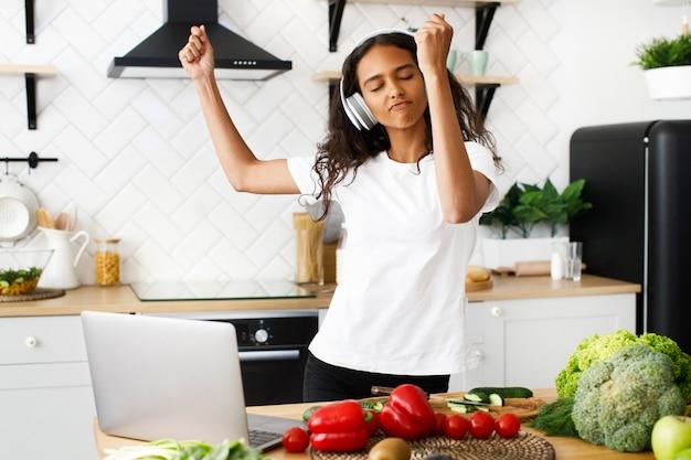Jovem mulher africana está dançando e ouvindo música através de fones de ouvido com os olhos fechados na cozinha Foto gratuita