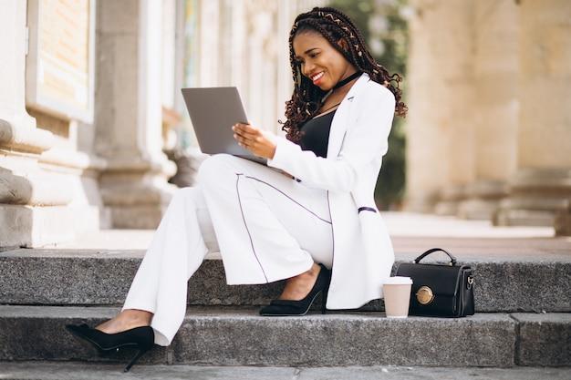 Jovem mulher africana vestida de branco usando laptop Foto gratuita