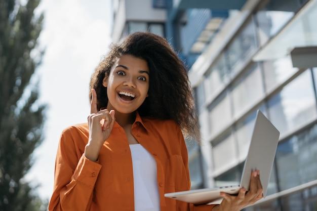 Jovem mulher afro-americana animada usando laptop, segurando o dedo, tendo uma idéia Foto Premium