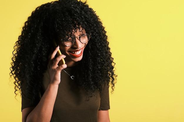 Jovem mulher afro-americana de cabelos cacheados usando seu telefone Foto Premium