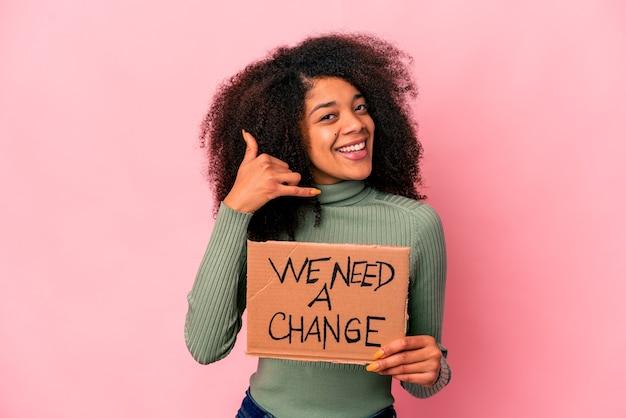 Jovem mulher afro-americana encaracolada segurando um precisamos de um cartão de mudança, mostrando um gesto de chamada de telefone móvel com os dedos. Foto Premium