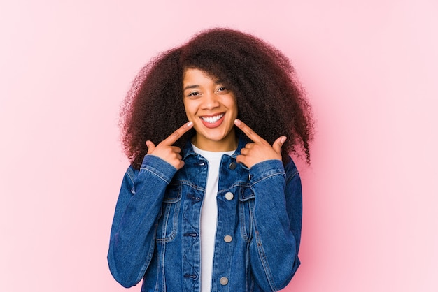 Jovem mulher afro-americana sorri, apontando os dedos na boca. Foto Premium