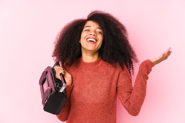 Jovem mulher afro segurando um cassete Foto Premium