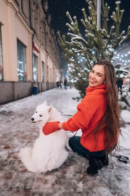 Jovem mulher agachada ao lado de um cachorro em uma rua de inverno Foto gratuita