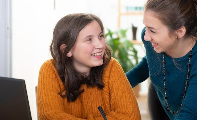 Jovem mulher ajuda uma menina adolescente com lição de casa Foto Premium