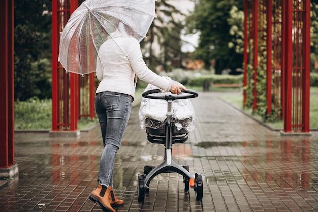 Jovem mulher andando com carrinho de bebê sob o guarda-chuva em um tempo raint Foto gratuita