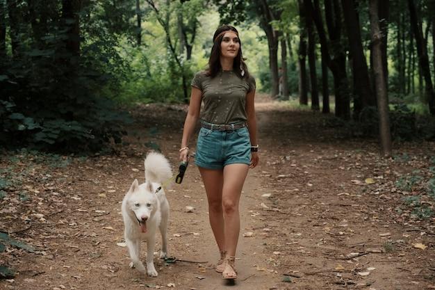 Jovem mulher andando com um husky branco Foto gratuita