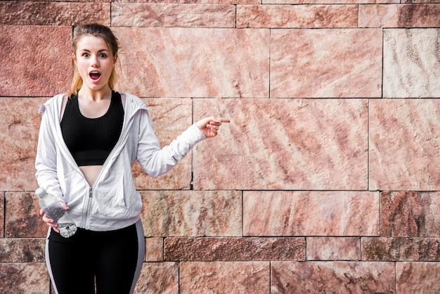 Jovem mulher apontando com o dedo Foto gratuita