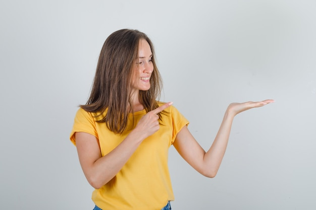 Jovem mulher apontando o dedo para a palma da mão levantada em uma camiseta, shorts e parecendo alegre Foto gratuita