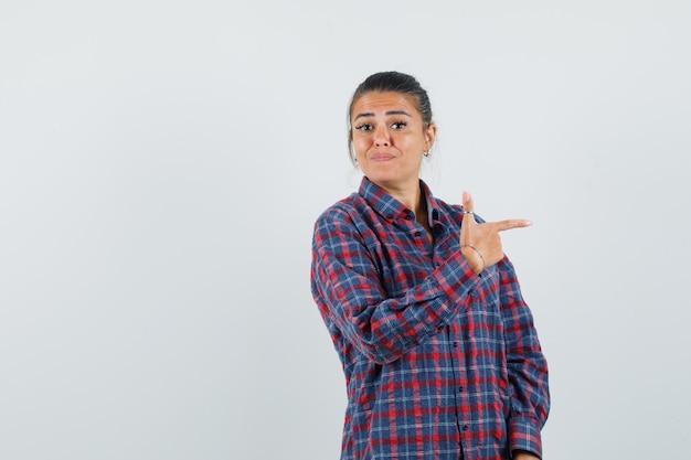 Jovem mulher apontando para a direita com o dedo indicador em uma camisa e olhando feliz, vista frontal. Foto gratuita