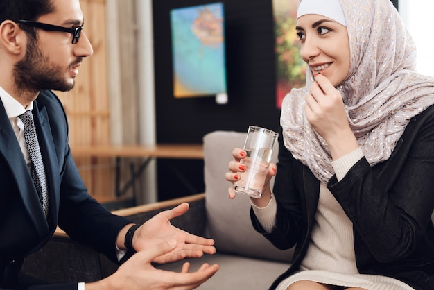 Jovem mulher árabe em hijab toma pílula. Foto Premium