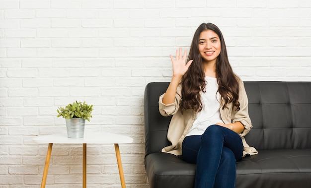 Jovem mulher árabe sentada no sofá sorrindo alegre mostrando número cinco com os dedos. Foto Premium